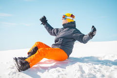 Excited male skier sitting on snow. Excited man skier sitting on snow Royalty Free Stock Image