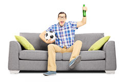 Excited male sport fan with ball and beer watching sport Stock Photos