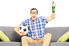 Excited male sport fan with soccer ball and beer watching sport Stock Photos
