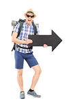 Excited male tourist holding a black arrow. Full length portrait of an excited male tourist holding a black arrow pointing right isolated on white background Royalty Free Stock Photos