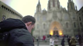 Excited male tourist taking picture of Gothic cathedral, travel impressions. Stock footage stock video footage
