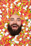 Excited man all covered with candies royalty free stock images