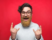 Rebellious man with golden beard on red. Excited man with beard in golden dust showing rock and roll gesture at camera on red backdrop stock photos