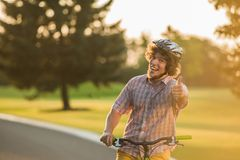 Excited man with bicycle outdoors. Portrait of joyful male person gesturing thumb up and smiling while relaxing with bicycle outdoors Stock Images