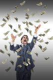 Excited man catching money falling around him. Businessman under money rain, yelling man reaching for flying banknotes Stock Photo