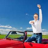 Excited man celebrating ownership of a cabriolet Stock Photo