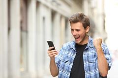 Excited man checking news on phone in the street. Excited man checking news on smart phone walking in the street stock photo