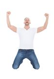 Excited man cheering in jubilation dropping down on his knees. With his fists raised in the air as he celebrates a success on white stock photo