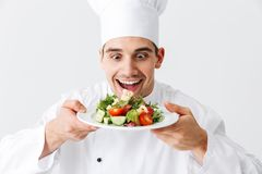 Excited man chef cook wearing uniform. Excited men chef cook wearing uniform showing fresh green salad on a plate isolated over white background royalty free stock photo