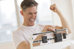 Excited Man Clenching Fist While Using Weight Scale. Excited mature man clenching fist while using balance weight scale at gym stock photography