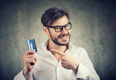 Excited man with credit card enjoying bank borrow. Young man in eyeglasses pointing at credit card in hands satisfied with choice of best bank royalty free stock photos