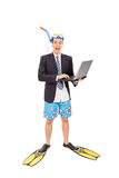 Excited man with diving mask working on laptop Royalty Free Stock Photo