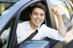 Excited man driving a car. Young man sitting in car Royalty Free Stock Photos