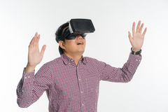 Excited man experiencing virtual reality via VR headset. And touching something with his hands on white background stock photo