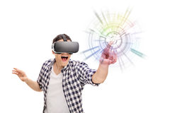 Excited man experiencing virtual reality. Young excited man experiencing virtual reality through VR headset isolated on white background Royalty Free Stock Images