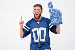 Excited man fan in blue t-shirt standing isolated. Image of screaming excited man fan in blue t-shirt standing isolated over white background. Eyes closed Stock Images