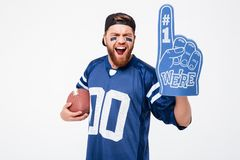 Excited man fan wearing fan glove holding rugby ball. Photo of excited man fan in blue t-shirt standing isolated over white background. Looking camera wearing Stock Photos