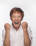 Excited man with fists raised and mouth open, studio shot Royalty Free Stock Photo