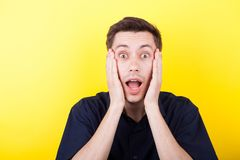 Excited man with hands on his face over yellow background. In studio photo Stock Photo