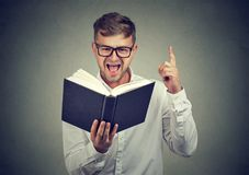 Excited man having answer in book stock photo