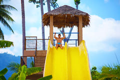 Excited man having fun on water slide in tropical aqua park Stock Images