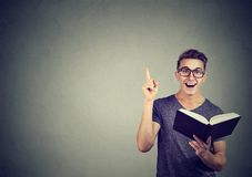 Excited man having idea while reading a book royalty free stock photo