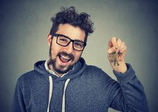 Excited man having new apartment. Young cheerful man in glasses boasting with key from new flat smiling at camera Royalty Free Stock Image