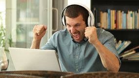 Excited man with headphones reading content on laptop. Excited man wearing headphones reading content on laptop finding offers sitting in a coffee shop stock video footage