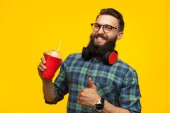 Excited man with healthy drink in studio. Young cheerful hipster man wearing headphones and showing thumb up holding cup of drink Royalty Free Stock Images