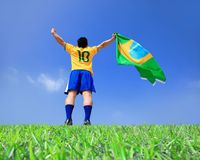 Excited man holding a brazil flag. With blue sky royalty free stock images