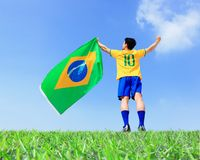 Excited man holding a brazil flag. With blue sky royalty free stock image