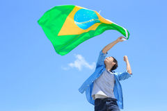 Excited man holding brazil flag. Excited man holding a brazil flag with blue sky Stock Photo