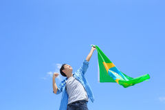 Excited man holding brazil flag. Excited man holding a brazil flag with blue sky royalty free stock photography
