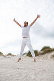 Excited man jumping on beach stock photos