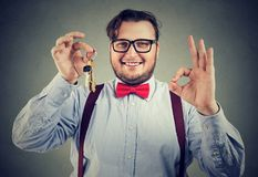 Excited man with keys from real estate. Successful man in bowtie showing OK gesture and bunch of keys from new flat Royalty Free Stock Images