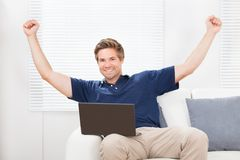 Excited man with laptop raising hands Stock Photos