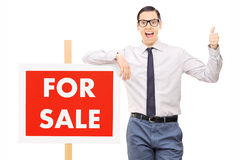 Excited man leaning on panel and giving thumb up Stock Photos