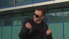 Excited man in leather jacket and sunglasses shouting yes reacting to winning or accomplishing something. Young very excited man in leather jacket and sunglasses stock footage