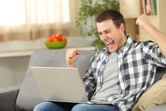 Excited man on line with a laptop at home Royalty Free Stock Photography