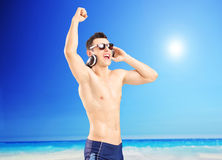 Excited man listening music and gesturing happiness, on a beach Royalty Free Stock Images