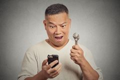Excited man looking at smartphone holding wrench key instrument Stock Photos