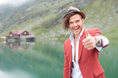 Excited man making the ok gesture near lake Stock Photo