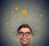 Excited man with many ideas light bulbs above head looking up Stock Image