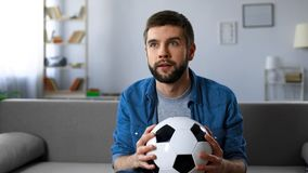 Excited man nervously watching football match on tv at home, end of first half. Stock photo Royalty Free Stock Photography