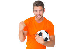 Excited man in orange cheering holding football Royalty Free Stock Image