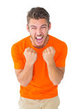 Excited man in orange cheering. On white background Royalty Free Stock Images