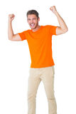 Excited man in orange cheering Stock Photos
