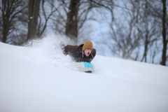 Excited man picking up more speed during sledding down a hill Royalty Free Stock Image