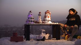 Excited man in pilot glasses and hood on bike. Man riding tricycle on grey sky. Holiday celebration concept. Christmas. And new year fun. Snowman and snow xmas stock video footage