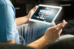 Excited man playing in an online casino with tablet. Stock Photography